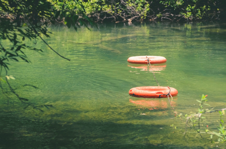 Life buoys floating on waters of Formoso river, a river with transparent green water surrounded by nature on Bonito MS, Brazil. Safety scenery. Stock Photo