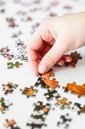 Hand of a woman playing Jigsaw Puzzle, starting to match the pieces to unveil the image. Pieces on a white background. Real game.
