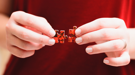 Jigsaw Puzzle Game: Hands of a woman holding and matching two pieces of a puzzle. Stock Photo