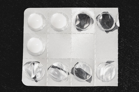 Used blister pack with some pills inside and others already used. Medicine, with a white rounded pills. Isolated, dark background. Stock Photo