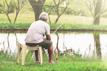 Retired old man seated next to the lake fishing and relaxing.