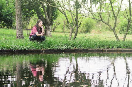 Woman fishing and relaxing, crouched in front of a lake, holding a bamboo fishing rod waiting patiently to catch a fish. Nature background with trees and water of the lake.