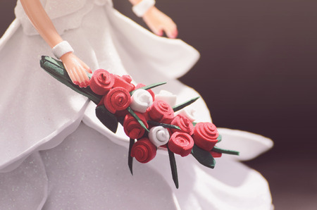 Hand of a doll bride holding a bouquet of flowers. Decorative wedding ornament background. Doll wearing a handcrafted white dress made of EVA foam.