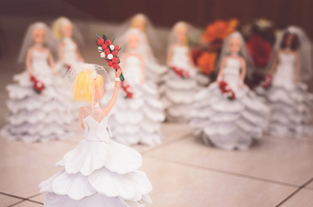 Decorative doll with a handcrafted white wedding dress holding high a bouquet of flowers ready to throw. Decorative wedding ornament.