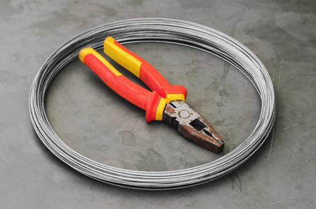 Coiled steel wire over a stone table with a used red plier on center. Carpentry and construction tools.