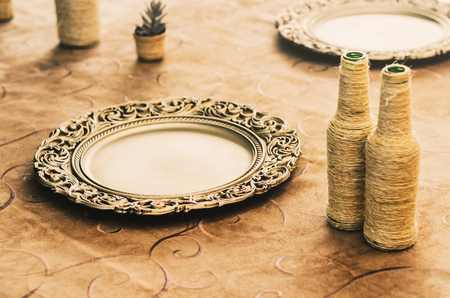 Table decoration with golden sousplat, some handcrafted bottles and ornaments over the table.