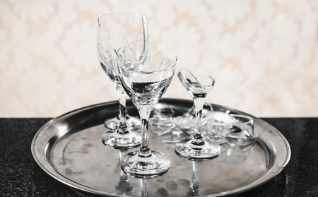 Tray with a broken wine glass on top of a balcony. Broken glass of a party or celebration.