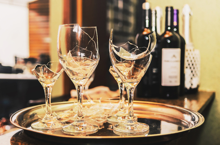 Broken wine glass on a tray with some wine and champagne bottles blurred on the background. Broken glass of a party or celebration.