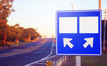 Road sign on a highway with two different choices of path and arrows left and right indicating the destination. Two blank choices with space for text. Stock Photo