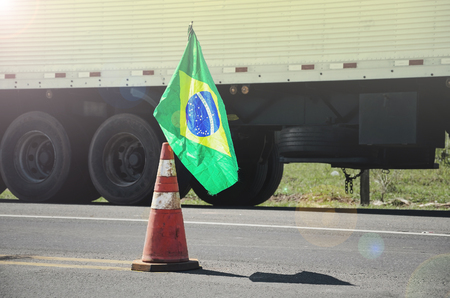 Brazilian flag on a red traffic cone of a highway with a blurred truck on background. Image concept to the stoppage and protest of the truck drivers on the highways of Brazil.