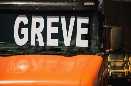 Trucker on strike. Orange truck with the windshield written Greve (in portuguese).