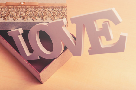 Word LOVE coming out of a craft box with the cover semi open. Concept of love for valentines day, mothers day, fathers day and general love.
