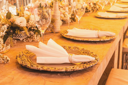 Table decoration with golden sousplat, napkin, glass cup, some handcrafted bottles, flower decoration and ornaments over the table. Stock Photo