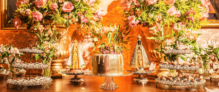 Candy table with a golden cake and some sweets around the cake of a wedding party. Flowers decoration and two Nossa Senhora Aparecida saints beside the cake. Golden decoration. Stock Photo