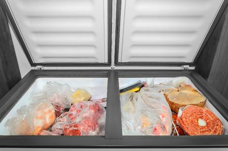 Alimenti congelati nel congelatore. Carne congelata insaccata e altri alimenti in un congelatore orizzontale con le due porte aperte. Conservazione del cibo.