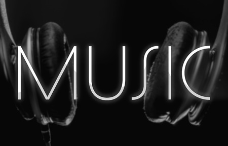 Music background. Blurred headphones on the background and the written Music on the front. Shining music word on a dark background.