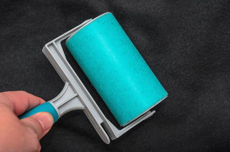 Using the sticky lint roller on a black fabric to remove dust, fur, hair of the shirt. Cleaning a fabric with a washable blue sticky roller.