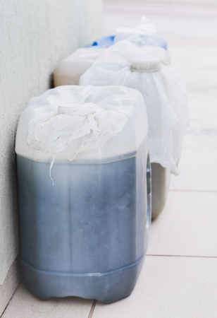 Household storage of gasoline in gallons for a possible lack of fuel. Plastic bag in the lid to not leak or evaporate gasoline. Stock Photo