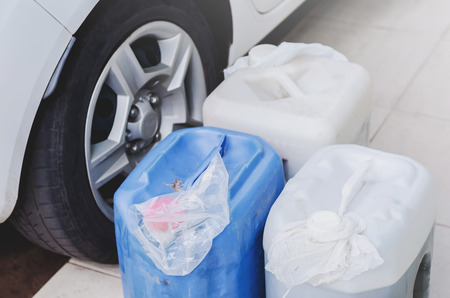 Household storage of gasoline in gallons for a possible lack of fuel. Gasoline in gallons next to a car, preventive act. Plastic bag in the lid to not leak or evaporate gasoline.
