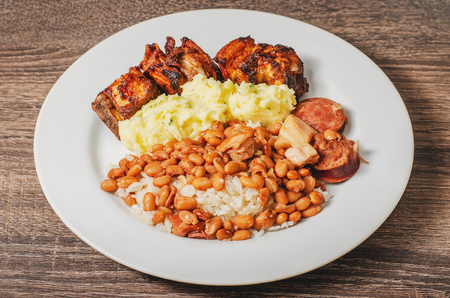 Brazilian cuisine, dish with rice and beans (arroz com feijao) seasoned with sausage and bacon, mashed potatoes and pork (costelinha de porco). White dish, daily typical brazilian food. Stock Photo