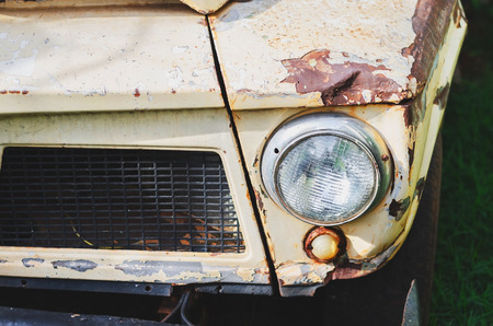 Close up on the headlight of a old pickup truck with a rusty bumper and painting. Beige color. Weathered vehicle with the painting oxidanting and peeling.