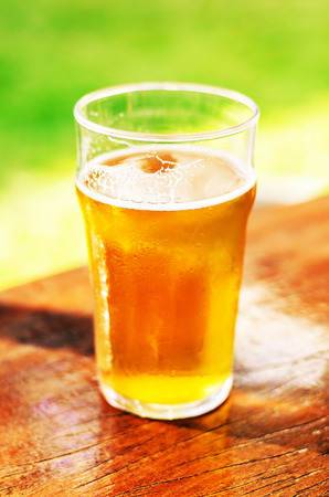 Glass of 500 ml of draft beer with no foam over a wooden table on a sunny day. Stock Photo