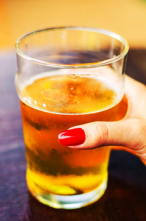 Hand of a woman holding a glass of 500 ml of draft beer with no foam over a wooden table of a sunny day.