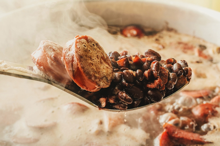 Spoon taking out of the pan ingredients of Feijoada, Brazilian cuisine. Spoon with black beans, pork meat and sausage. Feijoada cooking in the pan on the background with steam around.