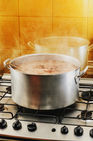 Cooking a big pan of Feijoada. Typical Brazilian cuisine, Feijoada has black beans, pork meat, bacon, sausage and spices. Cooking feijoada on a stove at home, homemade food.