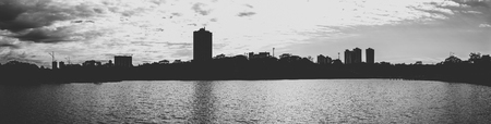 Silhouette of the lake and the city on the background on a cloudy day. Panoramic, black and white photo. Stock Photo