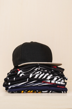 Pile of brand new t-shirts, dark tones, with print and a black cap over the pile. Blank space for text over the pile. Stock Photo