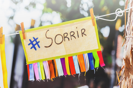 Colorful board with the message smile written in Brazilian portuguese suspended by a rope clamped with clips. Sorrir message, #sorrir, hashtag sorrir
