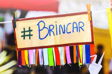Colorful board with the message play written in Brazilian portuguese suspended by a rope clamped with clips. Brincar message, #brincar, hashtag brincar, written brincar Stock Photo