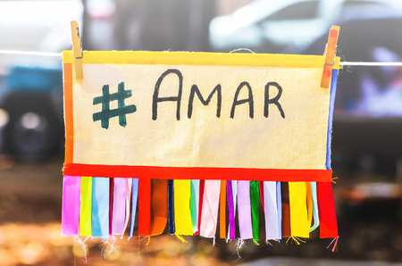 Colorful board with the message love written in Brazilian portuguese suspended by a rope clamped with clips. Amar message, #amar, hashtag amar, written amar in portuguese Stock Photo