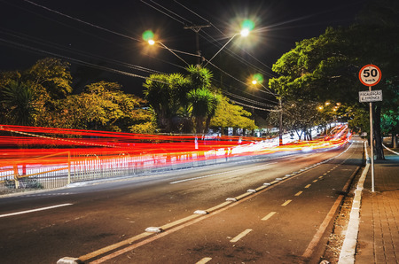 Long exposure photo of a street at night with a 50 kmh plate and a warning of electronic fiscalization written in Portuguese. Photo at Higienopolis avenue, Londrina - Parana, Brazil.