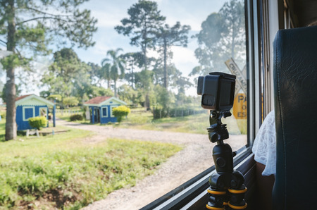 Recording the landscape of a train ride with a action camera on a tripod. Recording through the window of a train.