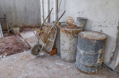 Residential construction equipments covered with cement on a construction site. Barrels, tubes, wheelbarrow, brick masonry.