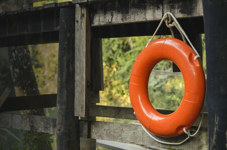 Orange life buoy suspended by its rope on a wooden bridge. Banco de Imagens
