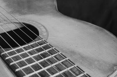 Szczegóły starej gitary akustycznej, krzywe ciała, otwór dźwiękowy, progi i nylonowe struny. Drewniana gitara akustyczna, zużyta i zakurzona. Czarno-białe zdjęcie makro, z głębią ostrości.