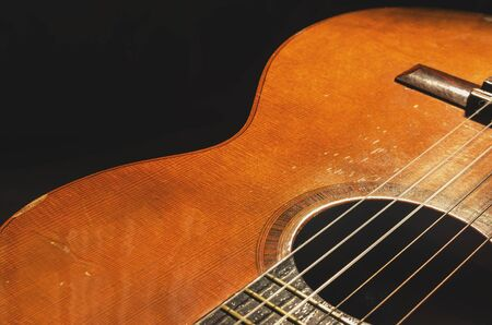 Shapes and lines of an old acoustic guitar, the body curves, sound hole, frets and old rusty nylon strings. Wooden acoustic guitar, worn out and dusty.