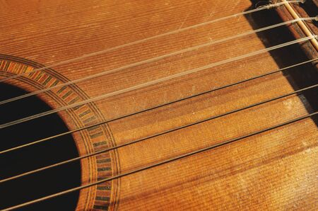 Shapes and lines of an old acoustic guitar, sound hole, part of the bridge and old rusty nylon strings. Wooden acoustic guitar, worn out and dusty.