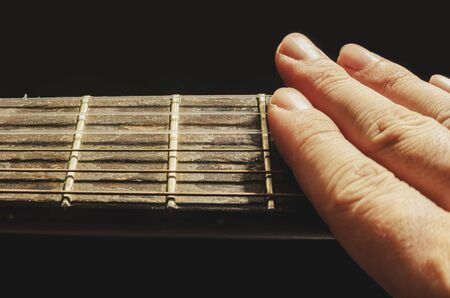 Fingers muffling the sound of the strings of an old acoustic guitar, isolated on a black background. Neck of an old acoustic guitar with frets and rusty nylon strings, worn out and dusty.