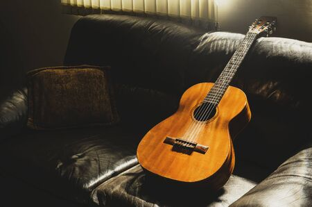 Old acoustic guitar leaning on the sofa at home illuminated by the sun light through the window. Music background.