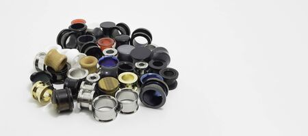 Ear stretchers: plugs and ear tunnels. Varied types, colors and sizes. Space for text.