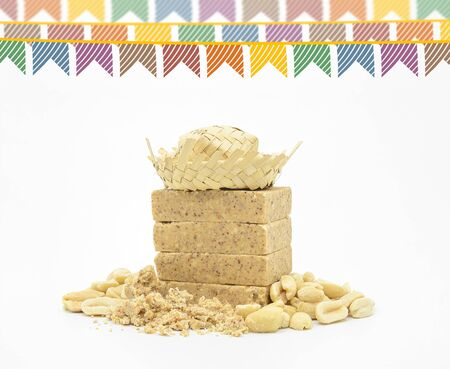 Pacoca, brazilian peanut candy with bran and some peanuts around. Festa Junina flags and a hillbilly hat. White background.