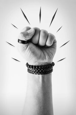 Raised fist, hand gesture with closed fist that express resistance and strength. Black and white.