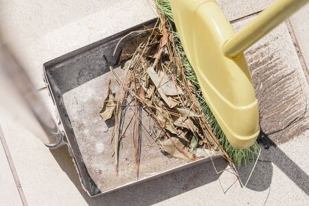 Collecting the dirt and some leaves of the sidewalk with a broom and a dustpan. Outdoors cleaning.