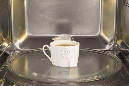 Tea cup inside the microwave. Warming the tea on the microwave.