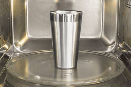 Aluminum cup inside the microwave. Warming the aluminum cup on the microwave. Not safe action. 版權商用圖片