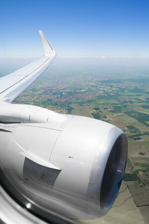 View through the window of an airplane during a flight over urban and rural areas during the day.